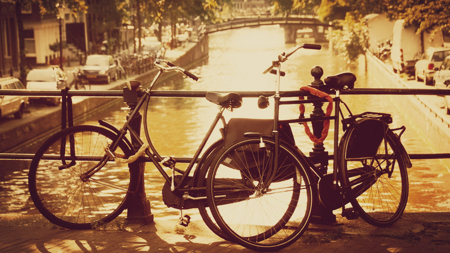 two bikes on a bridge over a canal in amsterdam