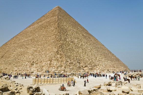 Tourists and natives are at the foot of an Egyptian pyramid